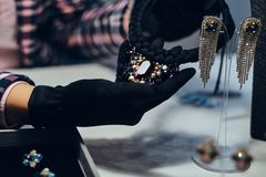 Close-up photo of a jewelry worker presenting a costly necklace with gemstones in a jewelry store. Close-up photo of a jewelry worker presenting a costly stock photo