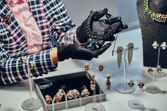 Close-up photo of a jewelry worker presenting a costly necklace with gemstones in a jewelry store. Close-up photo of a jewelry worker presenting a costly stock photos