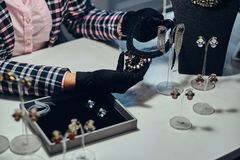Close-up photo of a jewelry worker presenting a costly necklace with gemstones in a jewelry store. Close-up photo of a jewelry worker presenting a costly stock photography