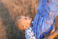Close-up of a happy little son hugging a tender mom on a blurred natural background. Childhood, family concept. A close-up photo of a joyful blond boy hugging Royalty Free Stock Photo