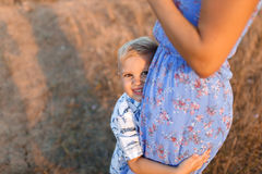 Close-up of a happy little son hugging a tender mom on a blurred natural background. Childhood, family concept. A close-up photo of a joyful blond boy hugging Stock Images
