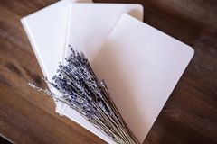 Close-up photo of light pink scheduler notebook on a wooden table with lavender. Flat lay composition Royalty Free Stock Photo