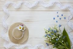 Close up photo with Little hat, lilies of the valley, and lace on a white wooden background, top view royalty free stock images