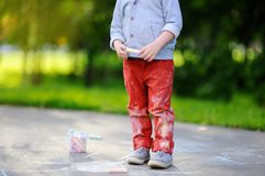 Close-up photo of little kid boy drawing with colored chalk on asphalt. Creative leisure for toddler child in summer park. Street art, kids education. Dirty Stock Image