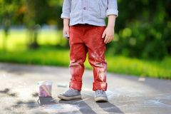 Close-up photo of little kid boy drawing with colored chalk on asphalt. Creative leisure for toddler child in summer park. Street art, kids education. Dirty Stock Photography