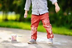 Close-up photo of little kid boy drawing with colored chalk on asphalt. Royalty Free Stock Image