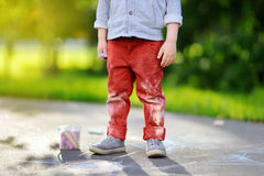 Close-up photo of little kid boy drawing with colored chalk on asphalt. Creative leisure for toddler child in summer park. Street art, kids education. Dirty Royalty Free Stock Photos