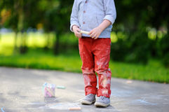 Close-up photo of little kid boy drawing with colored chalk on asphalt. Creative leisure for toddler child in summer park. Street art, kids education. Dirty Royalty Free Stock Photo