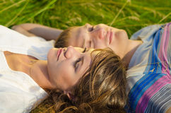 Close up photo of a loving couple lying in the grass Stock Images