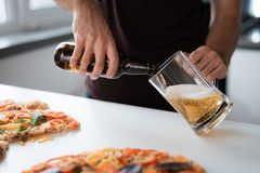 Close-up photo of a man pours beer into a glass. Next to the table is a pizza. Close-up photo of a man pours beer into a glass. Next to the white table is a royalty free stock images