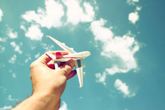 Close up photo of man's hand holding toy airplane against blue sky with clouds Stock Images