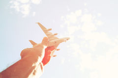 Close up photo of man's hand holding toy airplane against blue sky with clouds Stock Image