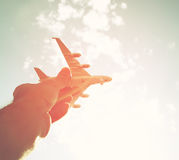 Close up photo of man's hand holding toy airplane against blue sky with clouds.  Royalty Free Stock Image