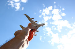 Close up photo of man's hand holding toy airplane against blue sky with clouds.  Stock Photography