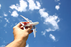 Close up photo of man's hand holding toy airplane against blue sky with clouds Royalty Free Stock Photo