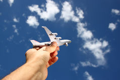 Close up photo of man's hand holding toy airplane against blue sky with clouds. filtered image.  royalty free stock images