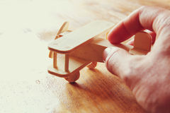 Close up photo of man's hand holding wooden  toy airplane over wooden background. filtered image. aspiration and simplicity concep Stock Images