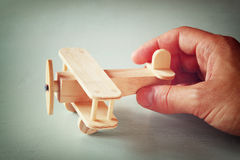 Close up photo of man's hand holding wooden toy airplane over wooden background. filtered image. aspiration and simplicity concept Royalty Free Stock Image