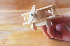Close up photo of man's hand holding wooden toy airplane over wooden background. filtered image. aspiration and simplicity concept Stock Image