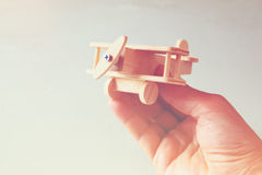 Close up photo of man's hand holding wooden toy airplane over wooden background. filtered image. aspiration and simplicity concept Stock Photos