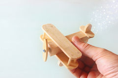 Close up photo of man's hand holding wooden toy airplane over wooden background. filtered image. aspiration and simplicity concept Stock Images