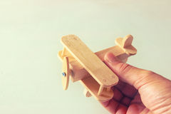 Close up photo of man's hand holding wooden toy airplane over wooden background. filtered image. aspiration and simplicity concept Royalty Free Stock Images