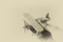 Close up photo of man's hand holding wooden toy airplane over wooden background. filtered image. aspiration and simplicity concept Stock Photography