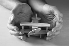 Close up photo of man's hand holding wooden toy airplane over wooden background. filtered image. aspiration and simplicity concept. Black and white old style royalty free stock image
