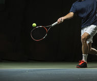 Close up photo of a man swinging a tennis racquet during a tennis match. Indoor court with a dark background Royalty Free Stock Images