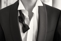 Close-up photo of man in tuxedo with open shirt and loose bow tie stock photo