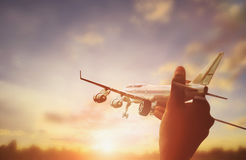 Close up photo of man's hand holding toy airplane and sunset Stock Images
