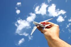 Close up photo of mans hand holding toy airplane against blue sky with clouds. filtered image.  royalty free stock images