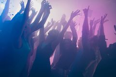 Close up photo of many birthday party people dancing clubbing purple lights confetti fog nightclub hands raised shiny