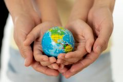 Mother and daughter holding world globe in eduction and protection concept stock images