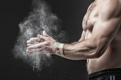 Close-up photo of a muscular torso and hands  on black b Royalty Free Stock Images