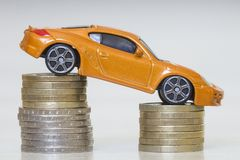 Close-up photo of new bright shiny yellow luxurious expensive to. Y sport car on two piles of metallic golden and silver coins as symbol of financial prosperity stock photo