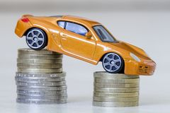 Close-up photo of new bright shiny yellow luxurious expensive to. Y sport car on two piles of metallic golden and silver coins as symbol of financial prosperity Royalty Free Stock Image