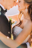 Close-up photo of newlywed young bride and groom with flower bouquet rubbing noses outdoors Royalty Free Stock Photo