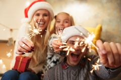 Close-up Photo Of Overjoyed Young Family Holding Sparkler While Royalty Free Stock Photos