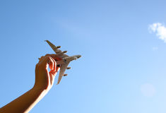 Close up photo ofwo man's hand holding toy airplane against blue sky with clouds. Close up photo of woman's hand holding toy airplane against blue sky with Royalty Free Stock Photography