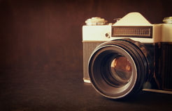 Close up photo of old camera lens over wooden table. image is retro filtered. selective focus Royalty Free Stock Image
