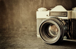 Close up photo of old camera lens over wooden table. image is retro filtered. selective focus.  royalty free stock image