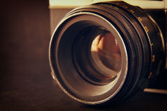 Close up photo of old camera lens over wooden table. image is retro filtered. selective focus. Stock Photos