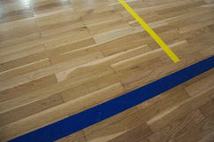 Close up photo of old parquet with lines in school sport gym. Royalty Free Stock Images