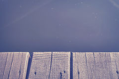 Close up photo of an old wooden pier by a lake. Vintage toned close up photo of an old wooden pier by a lake, background with space for text Royalty Free Stock Photography