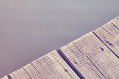 Close up photo of an old wooden pier by a lake. Vintage toned close up photo of an old wooden pier by a lake, background with space for text Royalty Free Stock Images