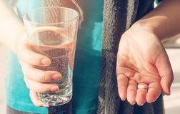Close up photo of one round white pill in young female hand. Woman takes medicines with glass of water. stock photography