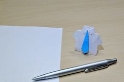 Close up photo of origami suit with blue tie near paper and pen on desk Royalty Free Stock Images