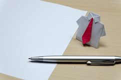 Close up photo of origami suit with pink tie near paper and pen on desk Royalty Free Stock Photo
