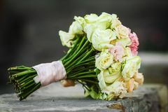 Close up photo of wedding bouquet laying on the stone. Close up photo of perfect beautiful wedding bouquet laying on the stone. bouquet includes white roses and stock photography